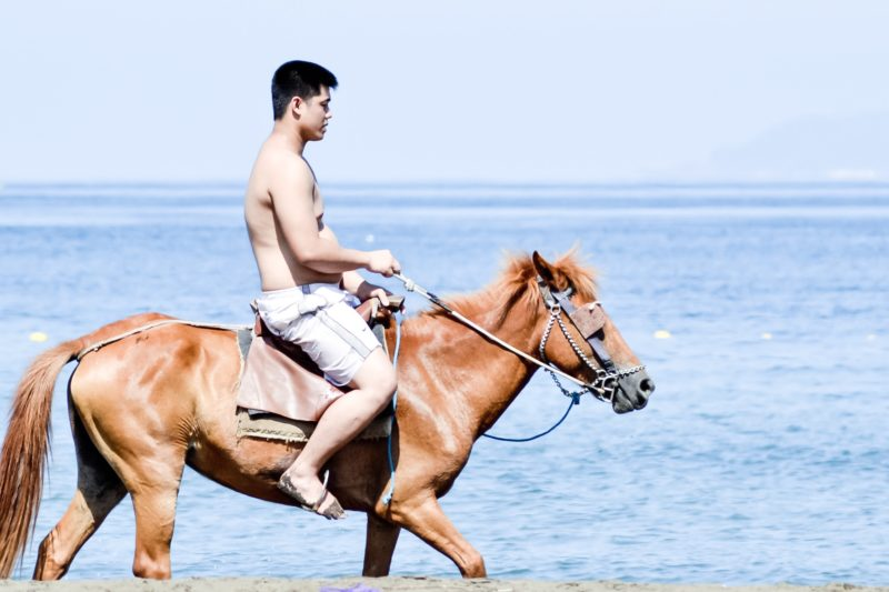 A man horseback riding beach